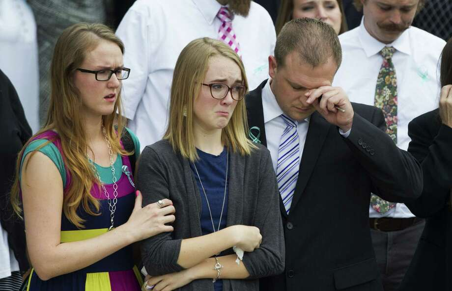 Cassidy Stay (center) leaves the Church of Jesus Christ of Latter-day Saints with other mourners after funeral services for members of her family. Photo: Brett Coomer / Houston Chronicle / © 2014 Houston Chronicle