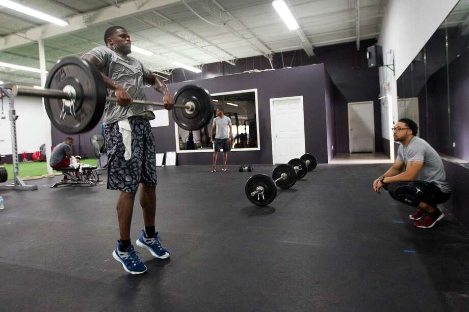 Texans wide receiver Andre Johnson, left, works with Abdul Foster, the brother of running back Arian Foster, at IX Innovations, a gym which opened earlier this year in the Galleria area. Photo: Brett Coomer, Staff / © 2014 Houston Chronicle