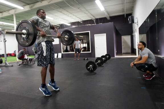 Texans wide receiver Andre Johnson, left, works with Abdul Foster, the brother of running back Arian Foster, at IX Innovations, a gym which opened earlier this year in the Galleria area.