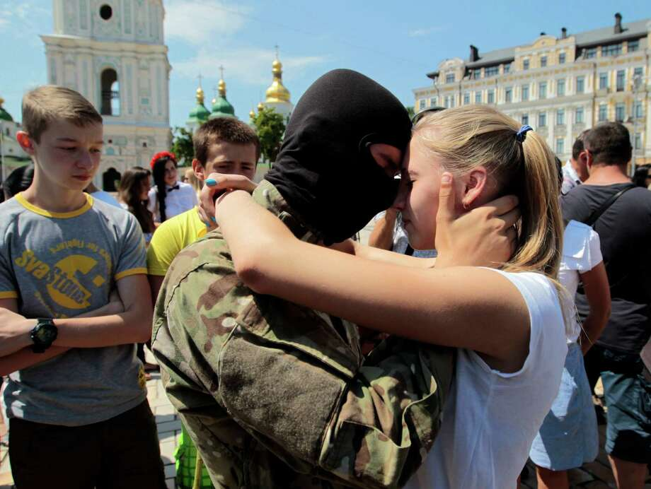 """A girl says goodbye to her friend, a volunteer, before they were sent to the eastern part of Ukraine to join the ranks of special battalion """"Azov"""", during a ceremony to take the oath of allegiance to Ukraine, in Kiev, Ukraine Wednesday, July 16, 2014. (AP Photo/Sergei Chuzavkov) ORG XMIT: XSC104 Photo: Sergei Chuzavkov / AP"""