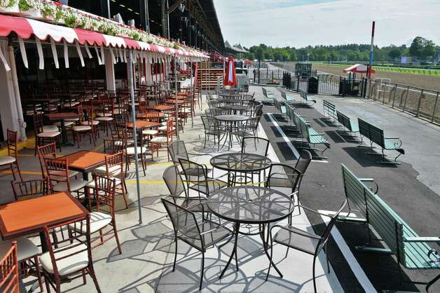 Clubhouse porch tables are expanded into the the traditional bench seating area at Saratoga Race Course Wednesday July 16, 2014, in Saratoga Springs, NY.  (John Carl D'Annibale / Times Union) Photo: John Carl D'Annibale / 00027812A