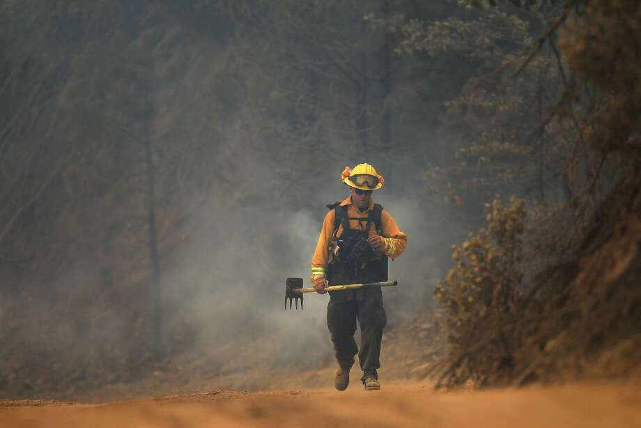 A firefighter walks on Bully Choop Road on Wednesday, July 16, 2014, on the Bully Fire near Ono, west of Redding, Calif. The fire, which authorities said was started by a marijuana grower who parked a rental truck in high grass, grew to 10,000 acres Wednesday. (AP Photo/Record Searchlight, Andreas Fuhrmann) Photo: Andreas Fuhrmann, Associated Press