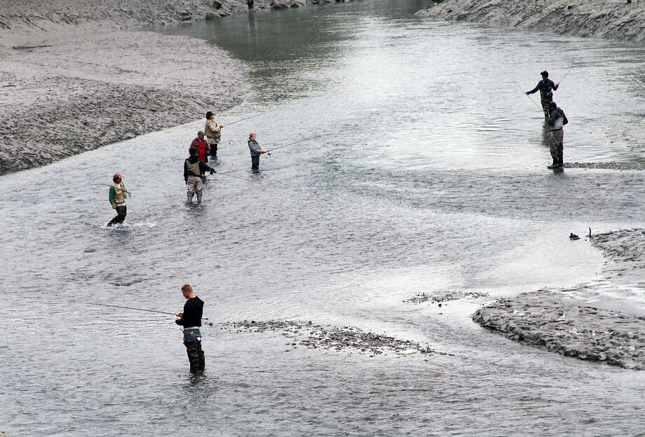 Anglers get in a little fishing early Wednesday morning, July 16, 2014, at Ship Creek in downtown Anchorage, Alaska (AP Photo/Mark Thiessen) Photo: Mark Thiessen, Associated Press