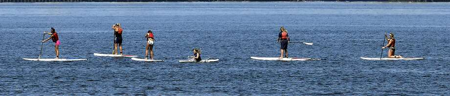 One paddle boarder in a line falls into the Puget Sound as the group begins their outing Wednesday, July 16, 2014, in Seattle. Temperatures topped out in the high 80's Wednesday, as slightly cooler weather and possibly even showers were expected in coming days in the area. (AP Photo/Elaine Thompson) Photo: Elaine Thompson, Associated Press