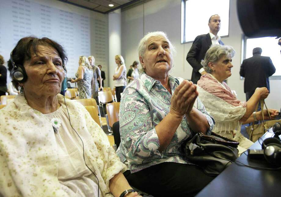 Bosnian women wait outside a court in the Netherlands. The court declared the Netherlands liable in the deaths of about 300 Bosnian Muslim men murdered by Serb forces in 1995. Photo: Associated Press / AP