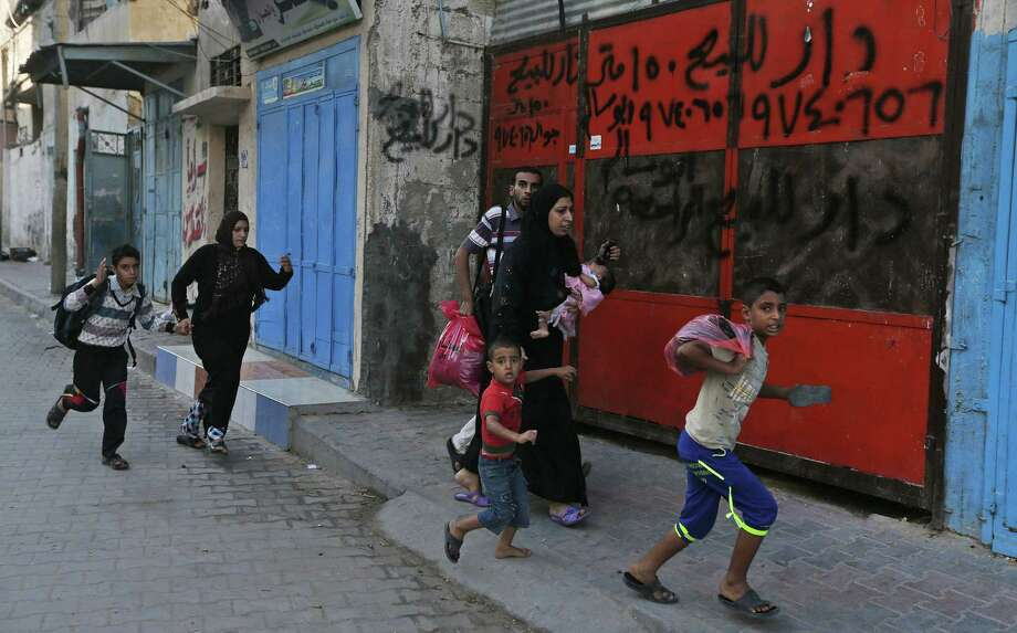 With the sounds of bombing in the distance, Palestinians flee their homes in Gaza City. Photo: Lefteris Pitarakis / Associated Press / AP