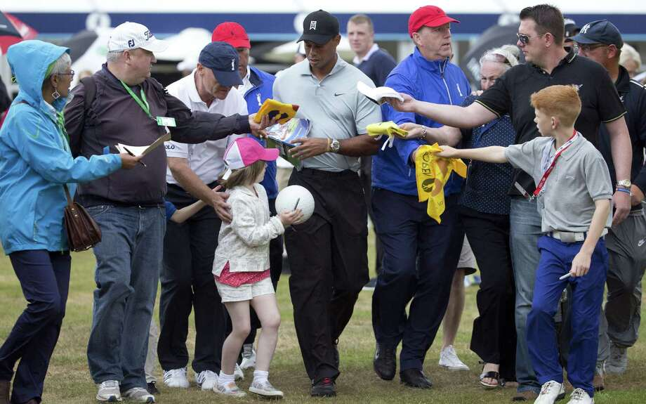 Tiger Woods, signing autographs after Wednesday's practice, has created a buzz around his first major of the year. Photo: Associated Press / AP