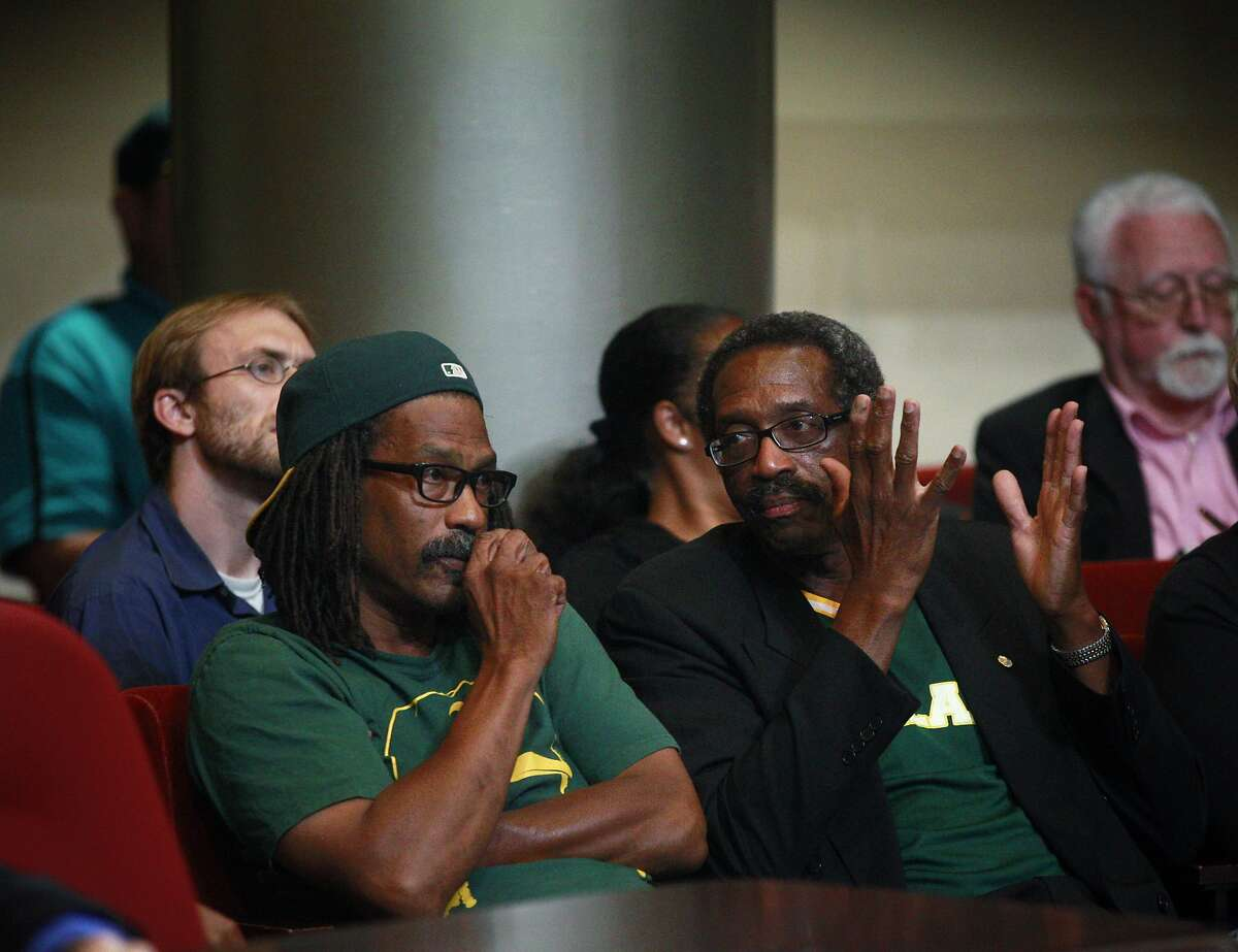 Darryl Stewart, left, and Nate Miley, the chair of the Oakland-Alameda County Coliseum Authority, right, react to the vote during Wednesday's council meeting. The Oakland City Council voted to revise the proposed lease agreement with the Oakland Athletics on Wednesday night, July 16, 2014, during a special session in Oakland, Calif. The revised lease must be approved bythe Coliseum Authorityand the Athletics now.