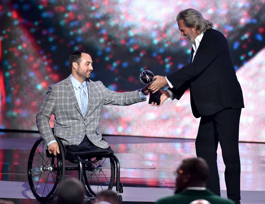 Olympic sledge hockey player Josh Sweeney accepts the Pat Tillman award from Jeff Bridges for service at the ESPY Awards at the Nokia Theatre on Wednesday, July 16, 2014, in Los Angeles. (Photo by John Shearer/Invision/AP) Photo: John Shearer, Associated Press