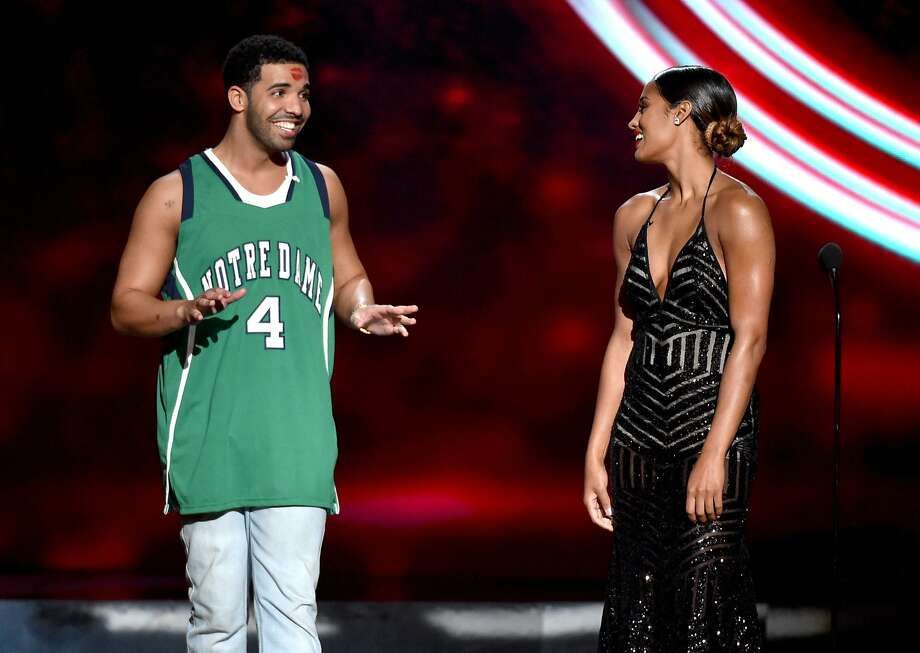 Skylar Diggins, right, smiles at Drake, left, who wears a Notre Dame jersey, at the ESPY Awards at the Nokia Theatre on Wednesday, July 16, 2014, in Los Angeles. Diggins played basketball at Notre Dame. (Photo by John Shearer/Invision/AP) Photo: John Shearer, Associated Press