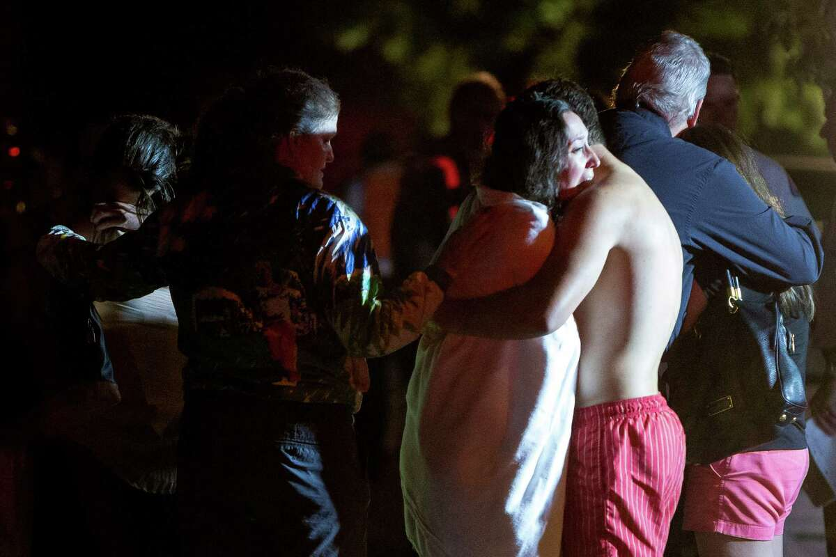 Victims and responders gather at the site of a motorboat versus sailboat collision around 10:30 PM Wednesday, July 16, 2014, on the western shores of Lake Washington in Seattle, Wash. At least four people involved in the crash were pulled from the water. Three people were listed in critical condition and transported to Harborview Medical Center, and a fourth victim died on scene.