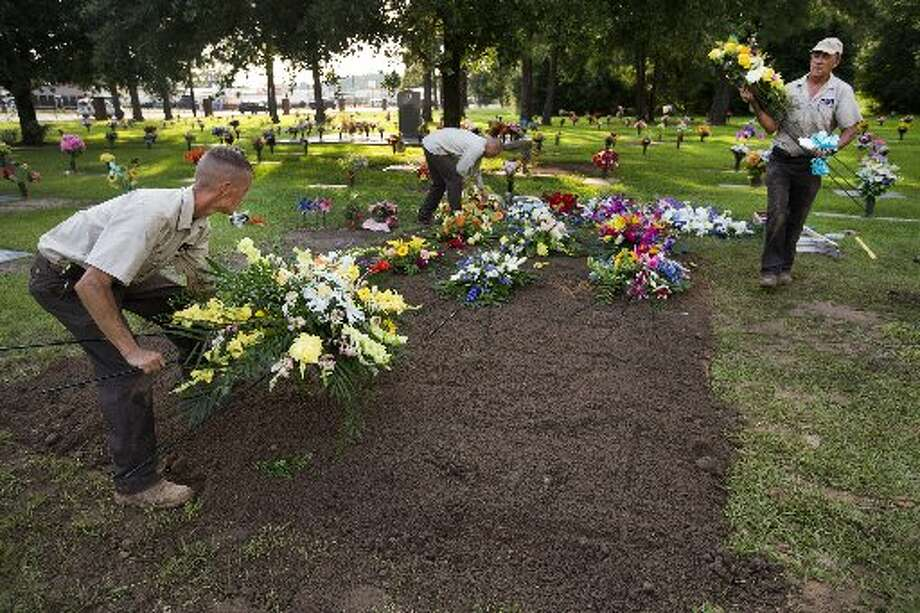 Paul Book, left, Jeremy Morin and Ronny Tubbs place flowers at the Stay grave site. Photo: Brett Coomer, Chronicle
