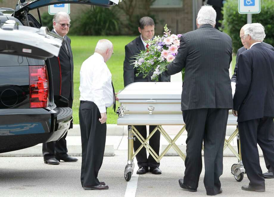 Flowers are placed onto one of six caskets before being taken into The Church of Jesus Christ of Latter-day Saints ,16331 Hafer Road, for the funeral service of six members of the Stay family  Wednesday, July 16, 2014. Photo: Melissa Phillip, Houston Chronicle / © 2014  Houston Chronicle
