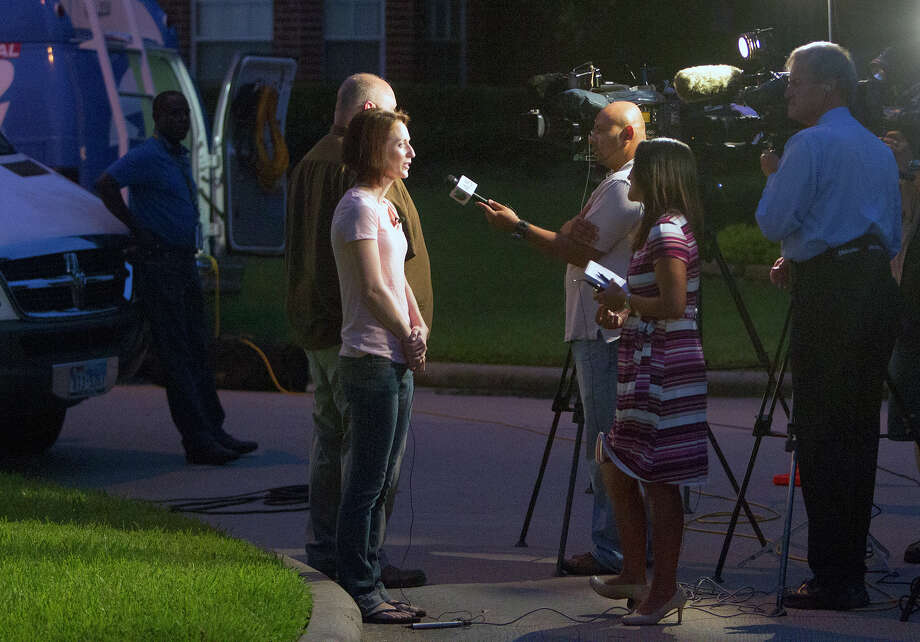 The media interviews, Moriah Davis, front, and Thomas Mixon, rear, in front of Don Guthrie's home, Wednesday, July 16, 2014, in Spring. Mixon is the former Scout leader for Bryan and friend to Stephen, and Moriah taught dance to Katie's children and saw them with great frequency. Photo: Cody Duty, Houston Chronicle / © 2014 Houston Chronicle
