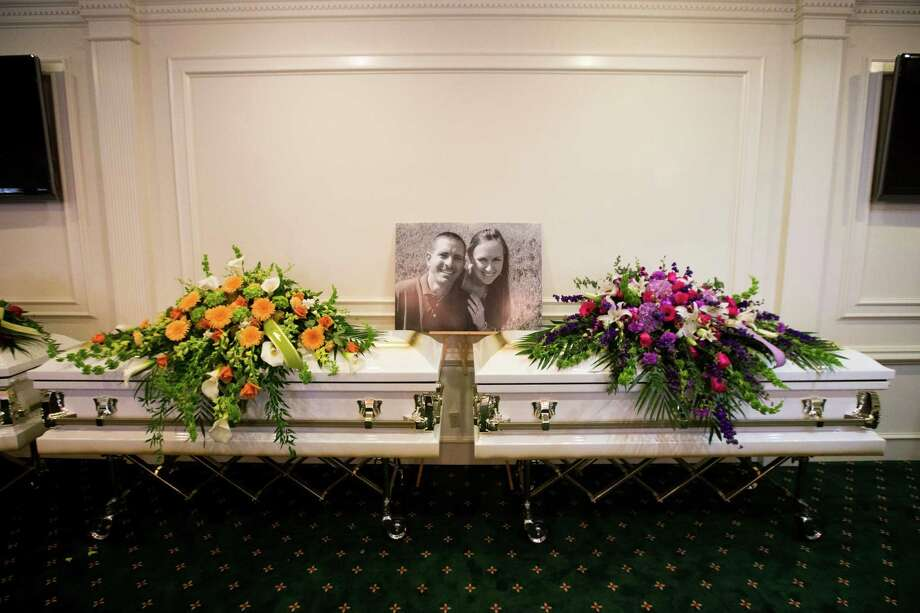 A photo of Stephen and Katie Stay is laid above their caskets before visitation at Klein Funeral Home Tuesday, July 15, 2014, in Spring. Photo: Brett Coomer, Houston Chronicle / © 2014 Houston Chronicle