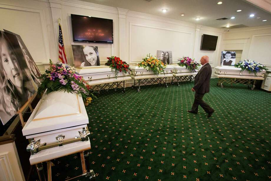 Funeral Director J.D. Baugus walks toward the six caskets of the Stay family before visitation at Klein Funeral Home Tuesday, July 15, 2014, in Houston. Photo: Brett Coomer, Houston Chronicle / © 2014 Houston Chronicle