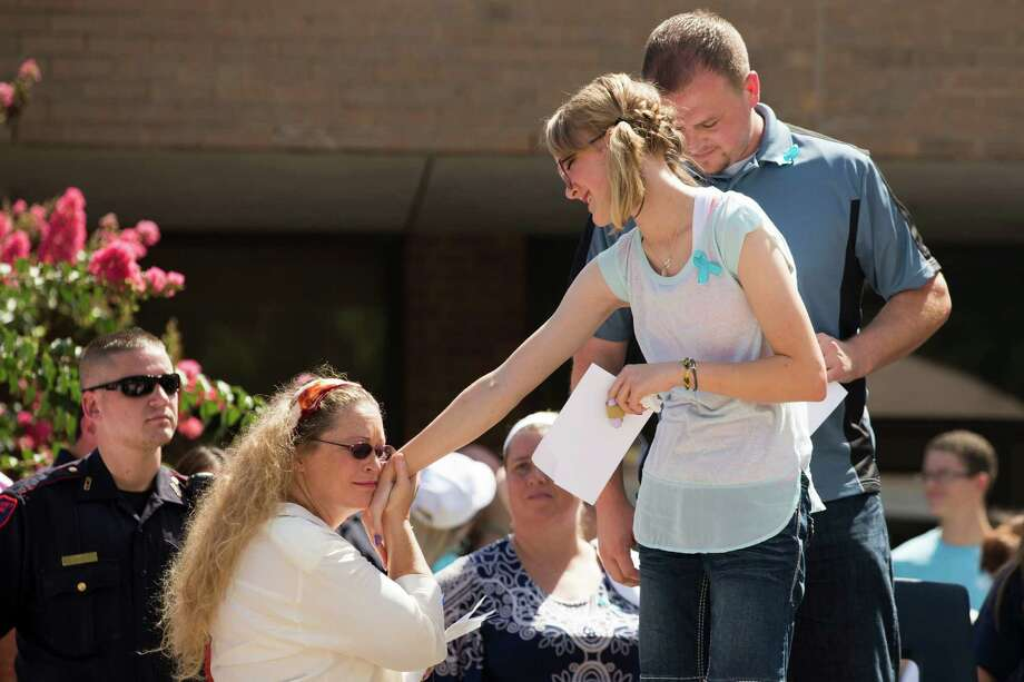 A supporter greets Cassidy Stay the lone survivor of the mass shooting of her parents and siblings, during a community memorial celebrating the lives of the Stay family at Lemm Elementary School Saturday, July 12, 2014, in Spring. Photo: Brett Coomer, Houston Chronicle / © 2014 Houston Chronicle