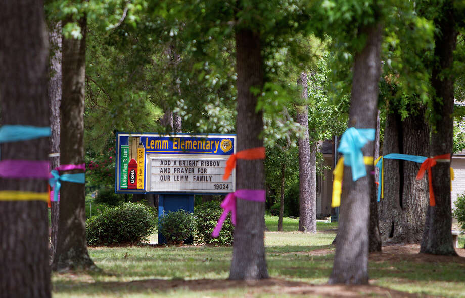 Ribbons are seen tied around trees in front of Lemm Elementary School, Thursday, July 10, 2014, in Spring. A shooting near the school took place Wednesday killing six people including four children and two adults, who were shot to death after an apparent domestic dispute. Some of the children attended the school. Photo: Cody Duty, Houston Chronicle / © 2014 Houston Chronicle