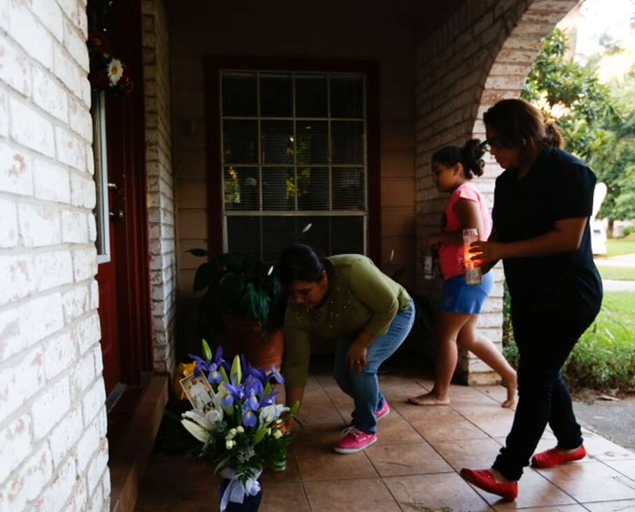 Elvia Palacios,  left, Anamari Palacios, 11, center, Viridiana Palacios, place candles on the front of a home where seven people were shot in Spring. Photo: Cody Duty / Houston Chronicle