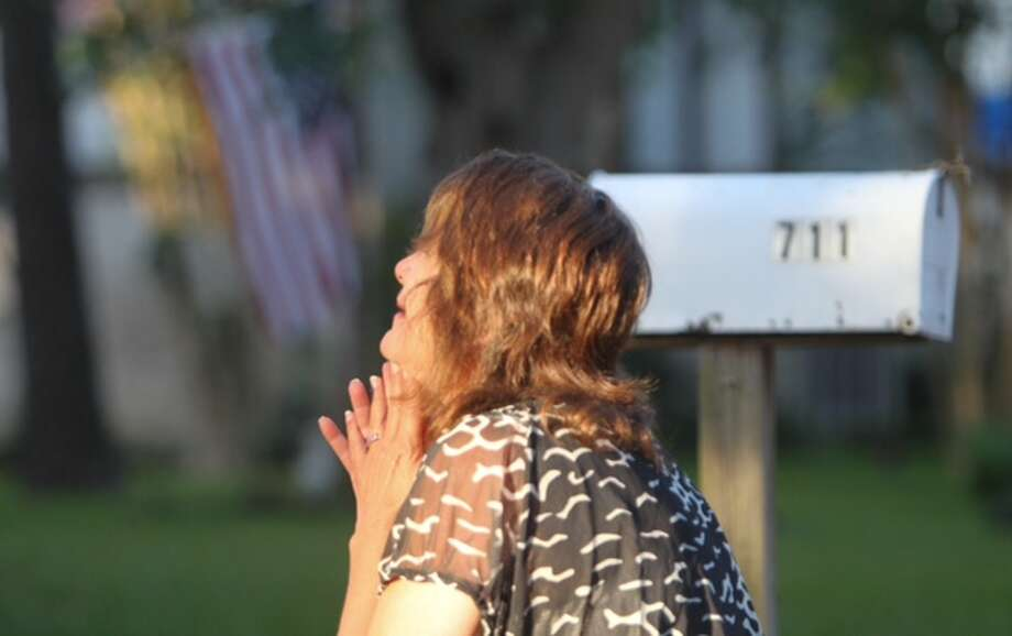 Patti Beller prays outside a home where seven people were shot on Wednesday in Spring. Photo: Cody Duty / Houston Chronicle