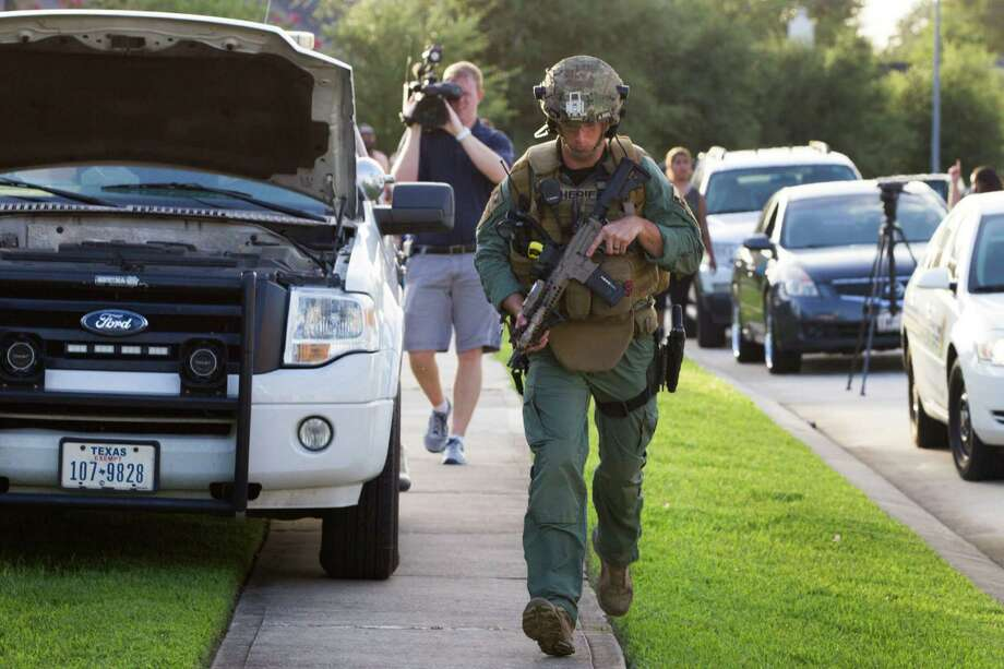 A law enforcement officer gears up for a standoff with a shooting suspect following a shooting Wednesday, July 9, 2014, in Spring. Seven people were shot, with six confirmed dead. Photo: Brett Coomer, Houston Chronicle / © 2014 Houston Chronicle