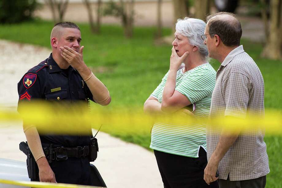 People stand with a law enforcement officer near the scene of a shooting Wednesday, July 9, 2014, in Spring. Seven people were shot, with six confirmed dead. Photo: Brett Coomer, Houston Chronicle / © 2014 Houston Chronicle