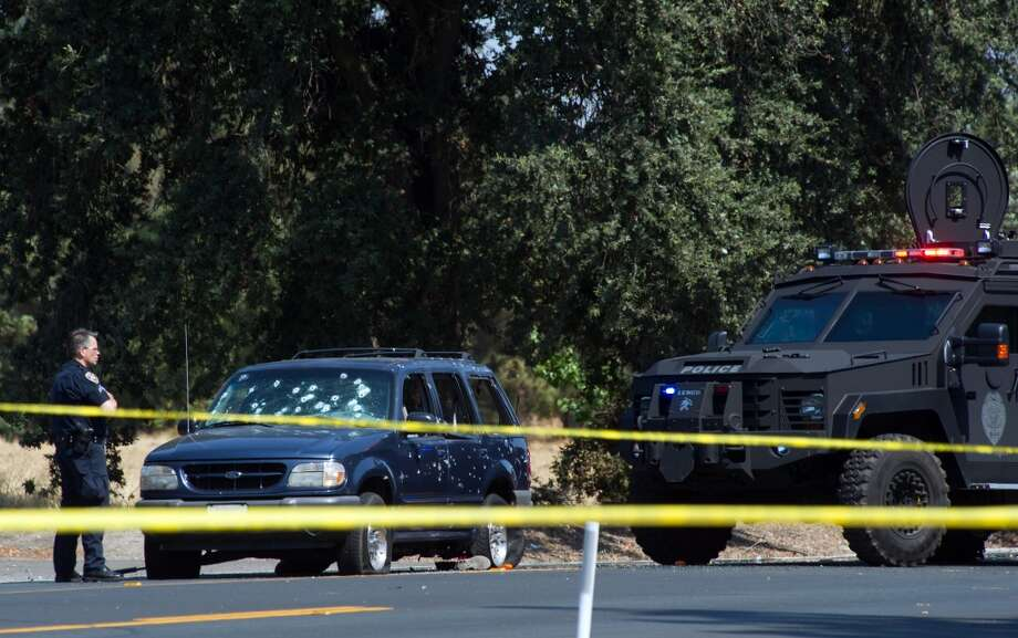 A Stockton Police officer investigates the scene after a vehicle involved in a suspected bank robbery was stopped on Wednesday, July 16, 2014, in Stockton, Calif. Three women were taken hostage by the robbers and two were thrown from their getaway vehicle. Police shot out the tires of the fleeing vehicle fatally wounding two suspects. Photo: Craig Sanders, Associated Press