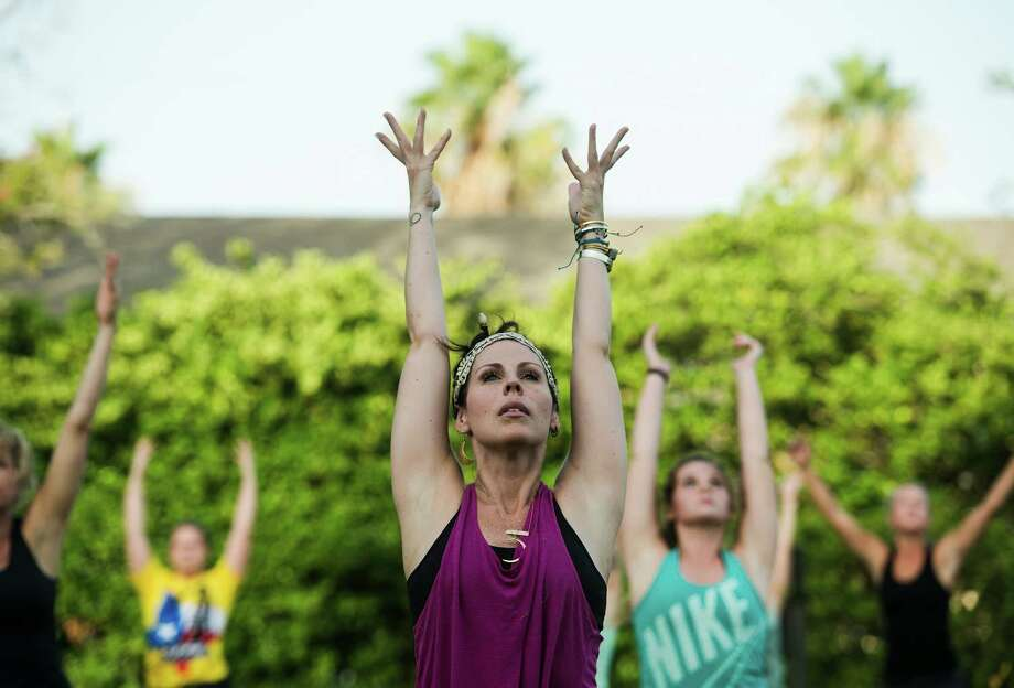 Tiffany Maloney of Love Yoga stretches her arms toward the open sky as she leads an outdoor class on the east lawn of the McFaddin-Ward House on Monday afternoon. The monthly class is called Monday at the Museums. Photo taken Monday 6/30/14 Jake Daniels/@JakeD_in_SETX Photo: Jake Daniels / ©2014 The Beaumont Enterprise/Jake Daniels