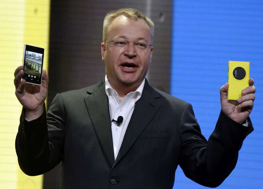 In this July 11, 2013 file photo, then Nokia CEO Stephen Elop shows the company's Nokia Lumia 1020, in New York. Elop, now Microsoft Executive Vice President, sent employees of the company's devices business a memo detailing its job cut plans. Microsoft on Thursday, July 17, 2014 said it would cut up to 18,000 jobs over the next year, with about 12,500 related to Microsoft's acquisition of Nokia's phone business in April. Photo: Richard Drew, Associated Press
