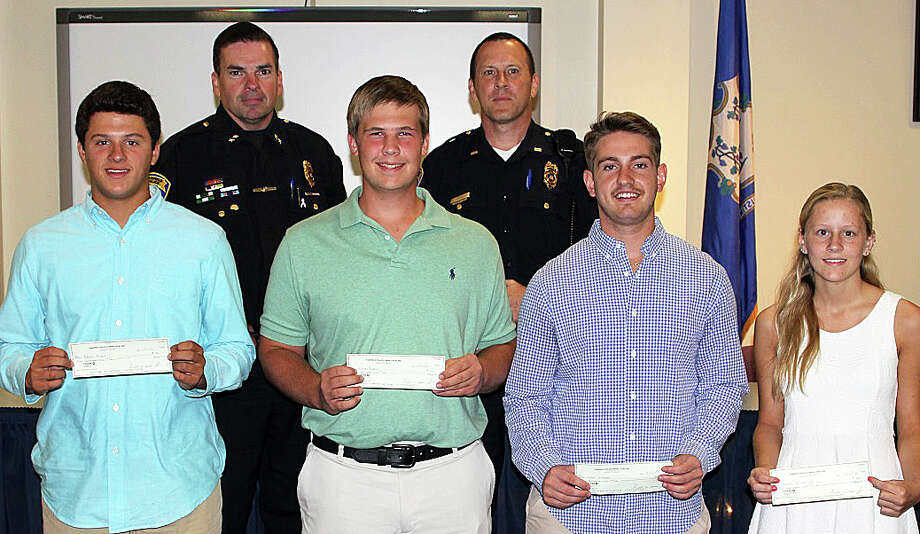 Four recipients of $500 scholarships from the Fairfield Police Union are, front row from left, Christopher Rubis, Christopher Bodnar, Tyler Caruso and Erin Broderick. Behind them are, from left, Police Chief Gary MacNamara and Lt. Keith Broderick, the union president. Photo: Contributed Photo / Fairfield Citizen