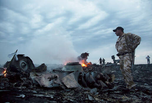 People walk amongst the debris, at the crash site of a passenger plane near the village of Grabovo, Ukraine, Thursday, July 17, 2014.  A Ukrainian official said a passenger plane carrying 295 people was shot down Thursday as it flew over the country and plumes of black smoke rose up near a rebel-held village in eastern Ukraine. Malaysia Airlines tweeted that it lost contact with one of its flights as it was traveling from Amsterdam to Kuala Lumpur over Ukrainian airspace. Photo: Dmitry Lovetsky, Associated Press / AP