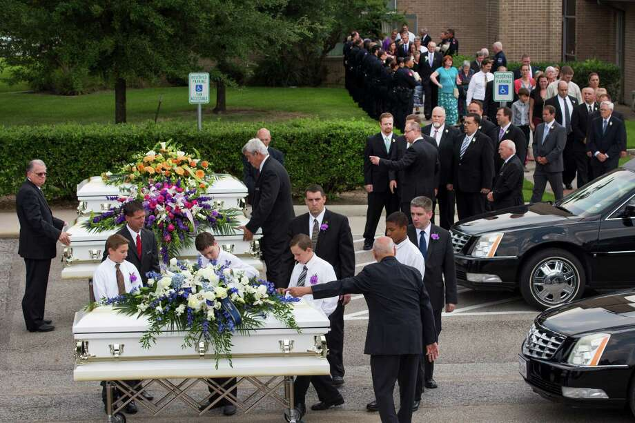 Caskets carrying the six members of the Stay family who were shot and killed last week are escorted after Wednesday's service. Photo: Brett Coomer, Staff / © 2014 Houston Chronicle