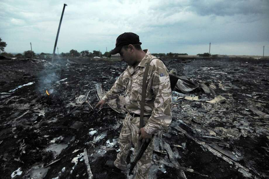 A man wearing military fatigues points to the wreckage of the malaysian airliner carrying 295 people from Amsterdam to Kuala Lumpur after it crashed, near the town of Shaktarsk, in rebel-held east Ukraine. Pro-Russian rebels fighting central Kiev authorities claimed on Thursday that the Malaysian airline that crashed in Ukraine had been shot down by a Ukrainian jet. Photo: DOMINIQUE FAGET, AFP / AFP