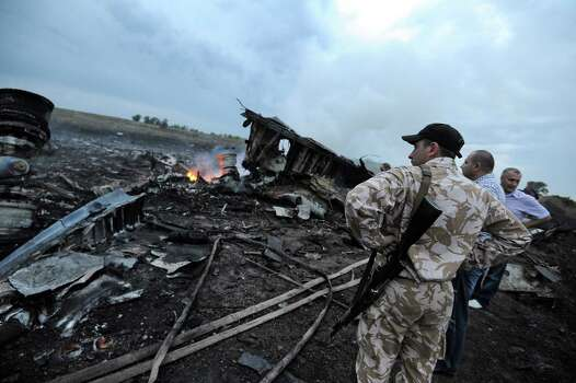 People stand next to the wreckages of the malaysian airliner carrying 295 people from Amsterdam to Kuala Lumpur after it crashed, near the town of Shaktarsk, in rebel-held east Ukraine, on July 17, 2014. Pro-Russian rebels fighting central Kiev authorities claimed on Thursday that the Malaysian airline that crashed in Ukraine had been shot down by a Ukrainian jet. Photo: DOMINIQUE FAGET, AFP / AFP