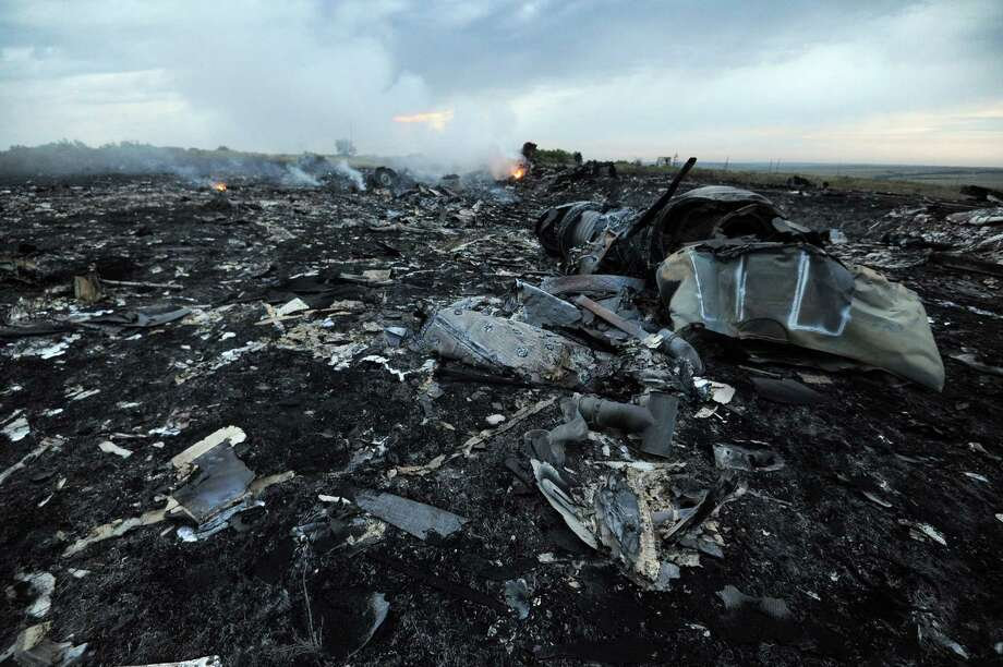 A picture taken on July 17, 2014 shows flames amongst the wreckages of the malaysian airliner carrying 295 people from Amsterdam to Kuala Lumpur after it crashed, near the town of Shaktarsk, in rebel-held east Ukraine. Pro-Russian rebels fighting central Kiev authorities claimed on Thursday that the Malaysian airline that crashed in Ukraine had been shot down by a Ukrainian jet. AFP PHOTO/DOMINIQUE FAGET Photo: DOMINIQUE FAGET, AFP / AFP