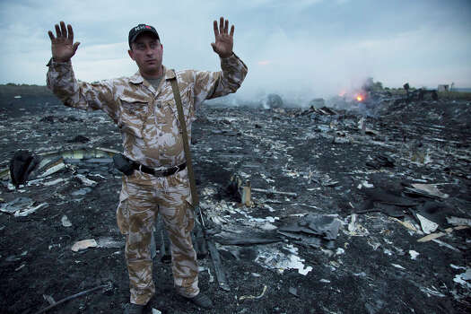 A man gestures at a crash site of a passenger plane near the village of Grabovo, Ukraine, Thursday, July 17, 2014. Ukraine said a passenger plane carrying 295 people was shot down Thursday as it flew over the country, and both the government and the pro-Russia separatists fighting in the region denied any responsibility for downing the plane. Photo: Dmitry Lovetsky, Wire Photos / AP2014