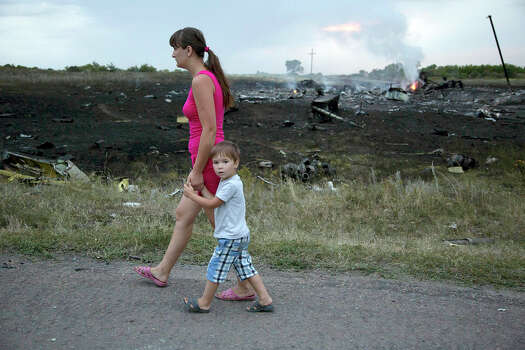 A woman with a child walks past the crash site of a passenger plane near the village of Grabovo, Ukraine, Thursday, July 17, 2014. Ukraine said a passenger plane carrying 295 people was shot down Thursday as it flew over the country, and both the government and the pro-Russia separatists fighting in the region denied any responsibility for downing the plane. Photo: Dmitry Lovetsky, Wire Photos / AP