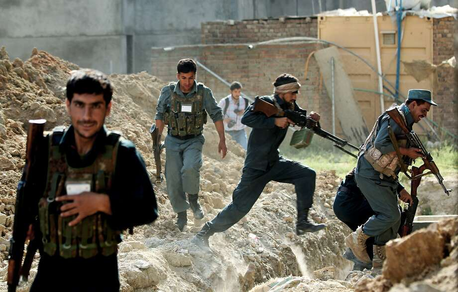 Security forces take cover during clashes with Taliban fighters at Kabul International Airport. Photo: Massoud Hossaini, Associated Press