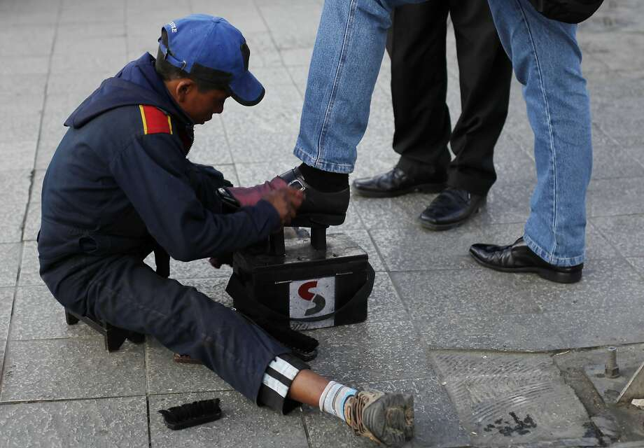 Lucas, 13, shines shoes in La Paz. Bolivia is the first nation to legalize child labor from age 10. The law offers safeguards, supporters say. Photo: Juan Karita, Associated Press
