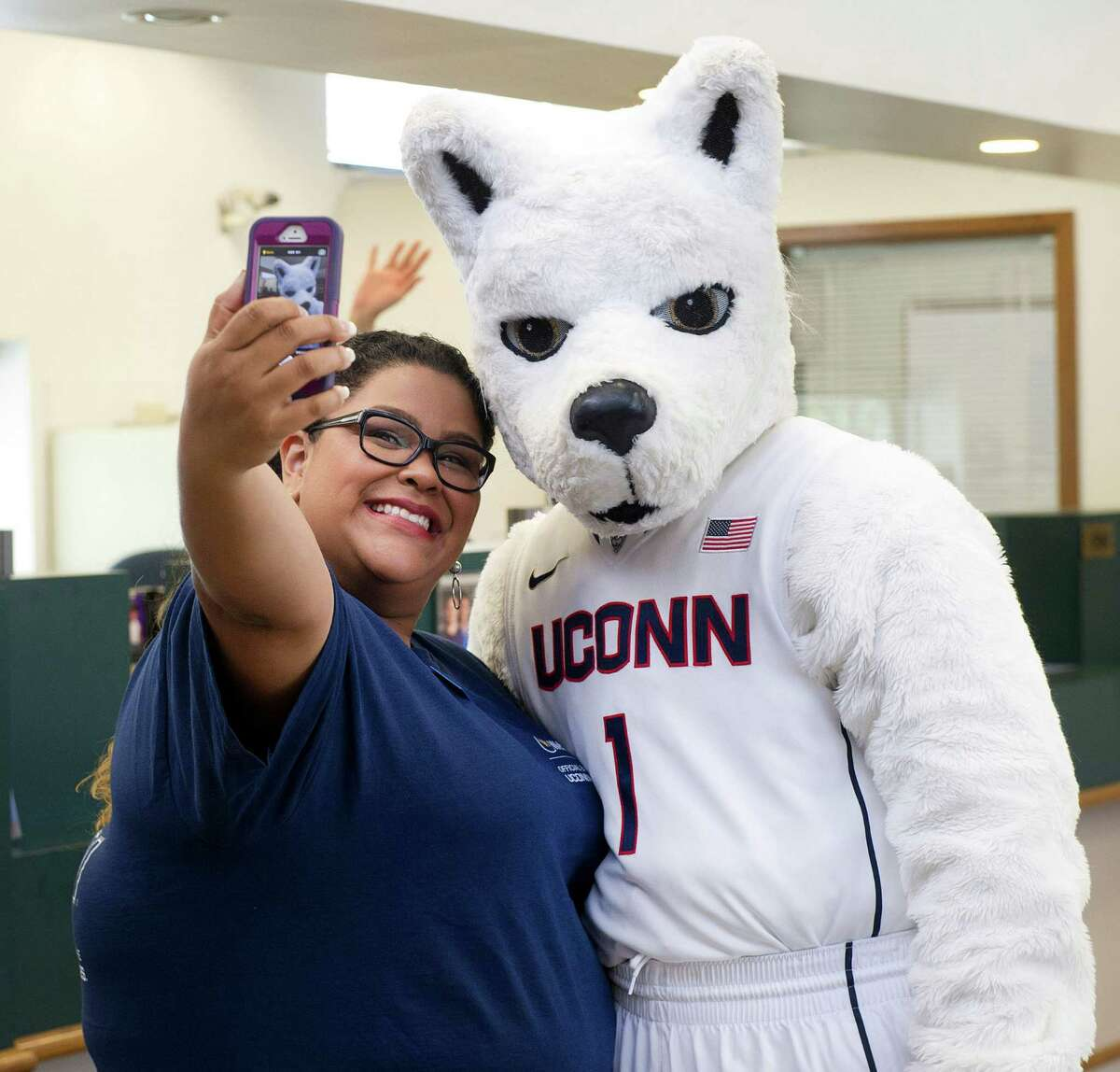Elizabeth Castillo takes a selfie with Jonathan the Husky at Webster Bank in Stamford, Conn., on Thursday, July 17, 2014.