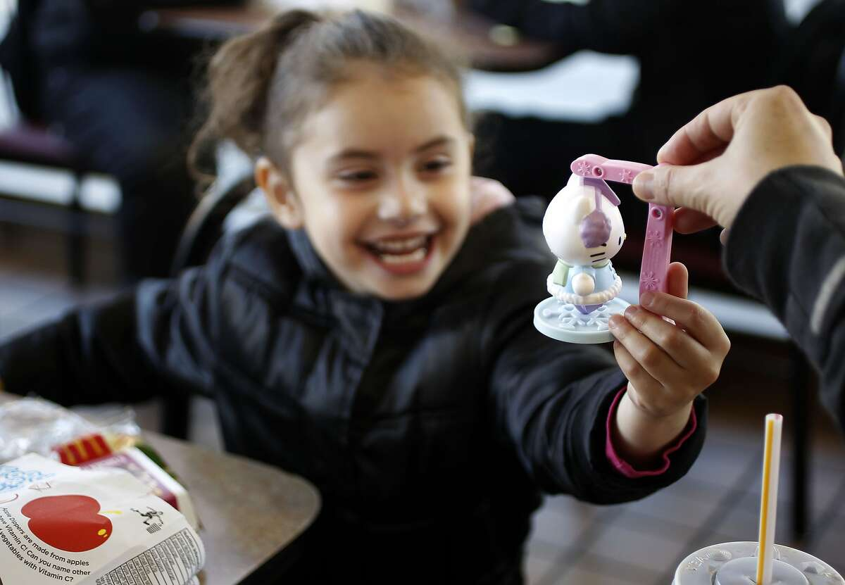 Hadara Chasky, 4-years-old reaches for her Hello Kitty toy from her brother as they eat their Happy Meals at ther McDonald's on the corner of 16th and Potrero streets in San Francisco, Ca., on Tuesday November 29, 2011. McDonald's is going to start charging customers for toys in Happy Meals starting December 1st of this year, as a way to comply with San Francisco's law that prohibits fast food restaurants from giving out free toys unless their meals meet strict standards.