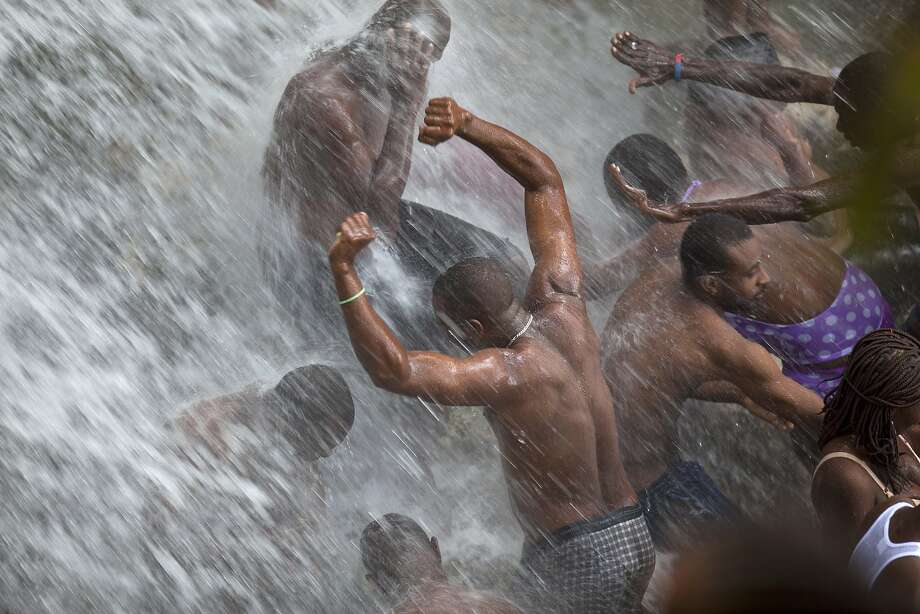 One of the premier voodoo swimming holes in Haiti: Christian and voodoo believers bathe in a waterfall at Saut d'Eau,  during an annual 