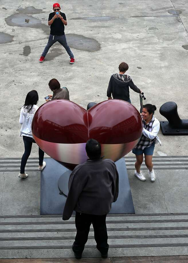"People pose for pictures with ""Open Heart,"" the newest piece of art at Pier 39 on Thursday, July 17, 2014 in San Francisco, Calif. The piece is part of a larger ""Hearts in San Francisco"" campaign put on by the San Francisco General Hospital Foundation that supports the programs of the hospital and trauma center. Photo: Kevin N. Hume, The Chronicle"