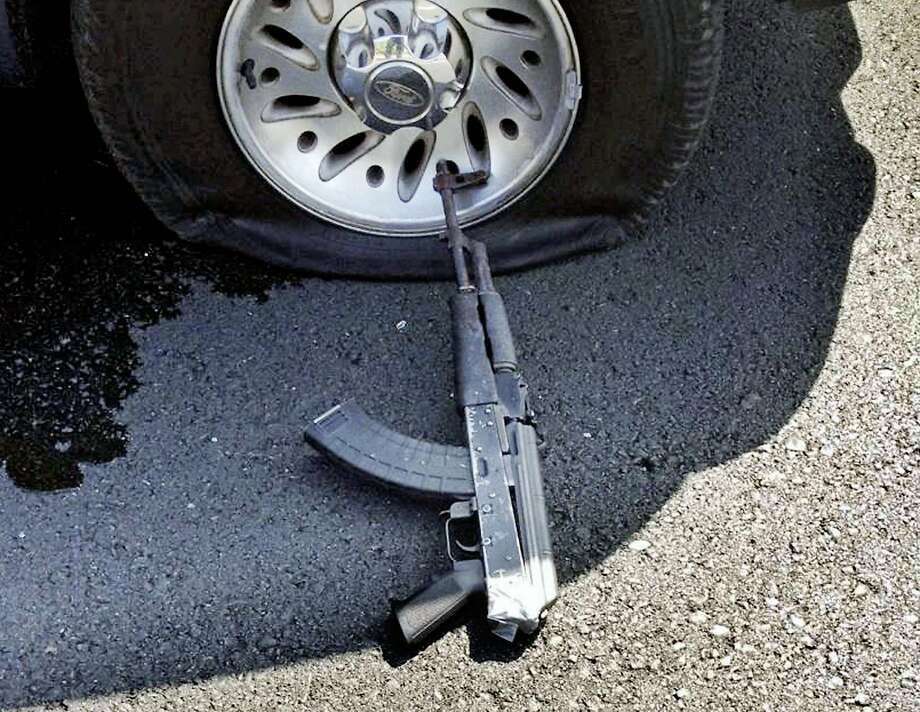 This photo provided by the Stockton Police Department shows a shot tire and firearm from the scene of a bank robbery Wednesday, July 16, 2014, in Stockton, Calif. Robbers fleeing a Stockton, California, bank took three women hostage and threw two of them from their getaway vehicle, as they fired repeatedly at police during a high-speed chase. Police shot out their tires but the shooting continued, fatally wounding two suspects and the last hostage. (AP Photo/Stockton Police Department) Photo: Associated Press
