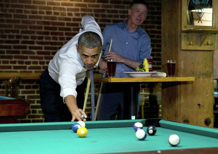 During a recent fundraising jaunt out West, President Barack Obama plays pool at a Denver bar with Colorado Gov. John Hickenlooper (right). He continues to avoid visiting the border. Photo: Jacquelyn Martin / Associated Press / AP