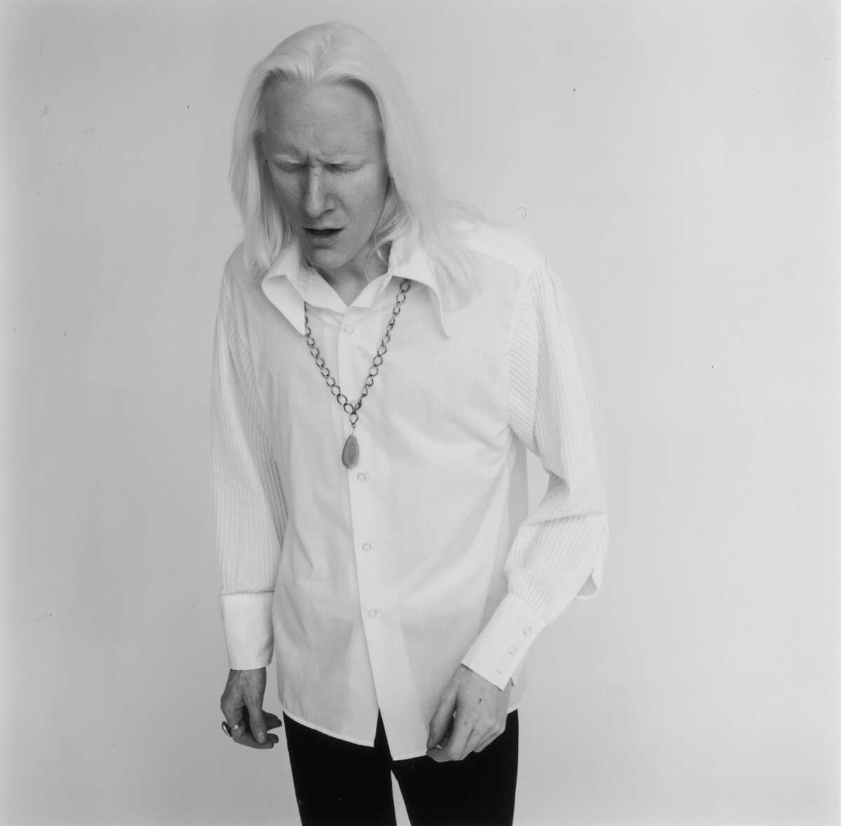 3rd May 1969: Studio portrait of American blues and rock guitarist Johnny Winter, looking down. He wears a necklace and a white shirt. (Photo by Jack Robinson/Hulton Archive/Getty Images)