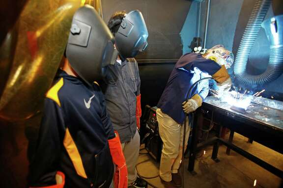 Jose Henner, left, a junior at Nimitz High School, and Alejandro Ibarra, a senior at Sam Houston Math, Science and Technology Center, watch as Alberto Urbina does a welding demonstration.