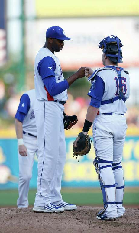 Skeeters pitcher Tracy McGrady, left, shares a fist bump with catcher Travis Scott before exiting the Atlantic League All-Star Game and baseball Wednesday. Photo: Karen Warren, Staff / © 2014 Houston Chronicle