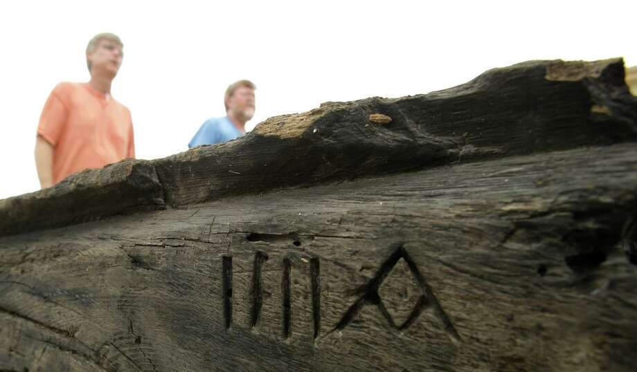 """Texas A&M researchers pass above a fore foot piece of the keel of the 300-year old ship La Belle Thursday, July 17, 2014, in Bryan, Texas. The Roman numeral IIII beside the letter """"A"""" told the builders in 1864 where this piece of the ship's frame belonged.  The remains are being transferred from a gigantic preservation-aiding freeze-dryer at Texas A&M University to the state museum in Austin for reassembly. Looking for the Mississipi river in 1685 French explorer La Salle and his ship ended up in the Gulf of Mexico where La Belle sank in a storm off the coast of Texas. She was found in 1995 under 12 feet of water. Photo: Pat Sullivan, Associated Press / AP"""