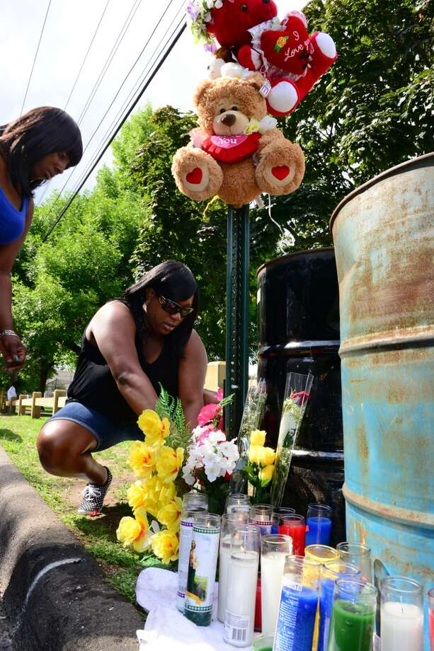 On Thursday July 17, 2014, friends came to place candles and flowers nearby the spot where shooting victim Joseph Myers was murdered on Jefferson Street in Bridgeport, Conn. Myers was brutally shot in the back of his head Wednesday night while he sat in the back of his Honda Civic. Photo: Christian Abraham
